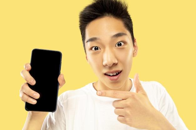 Ritratto del giovane coreano. modello maschile in camicia bianca. utilizzo dello smartphone per scommettere, leggere notizie o parlare. concetto di emozioni umane, espressione facciale. Foto Gratuite