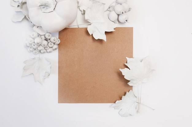 Kraft sheet of paper, white pumpkin, berries and leaves on a whitebackground. Premium Photo
