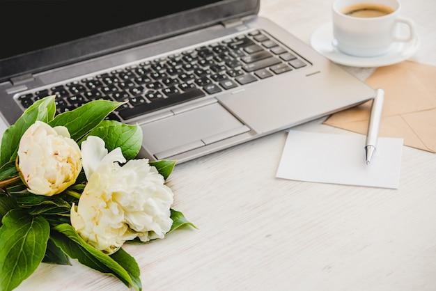Взгляд со стороны палубы с компьютером, букета цветков пионов, чашки кофе, пустой карточки и конверта kraft. Premium Фотографии