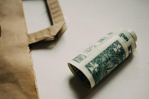 白いテクスチャの背景にkraftパッケージで現金ドルのお金。 Premium写真