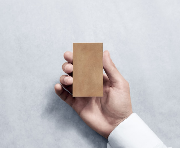 Рука держа пустой вертикальный дизайн визитной карточки kraft. Premium Фотографии