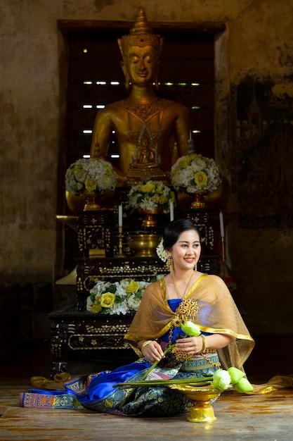 タイのドレスを着た女性が座って、蓮の花を折り、寺院の僧ksたちに捧げます。 Premium写真