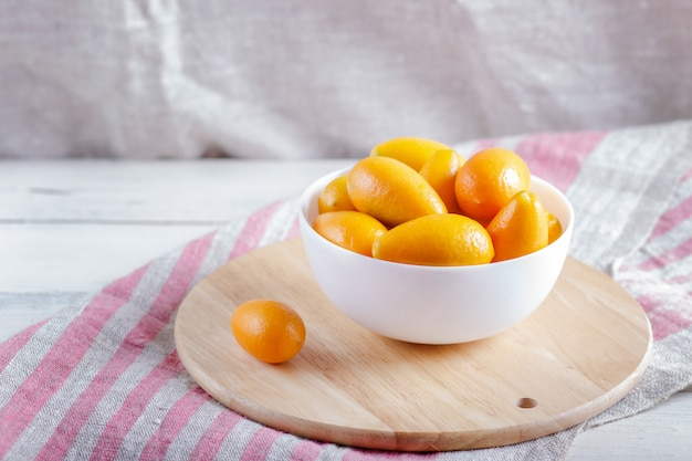 Kumquats in a white plate on  a wooden kitchen board Premium Photo