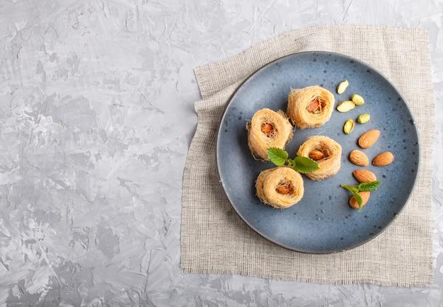 Kunafa, traditional arabic sweets in blue ceramic plate top view. Premium Photo