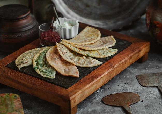 Kutab varieties on a steak board with sumakh and yogurt. Free Photo