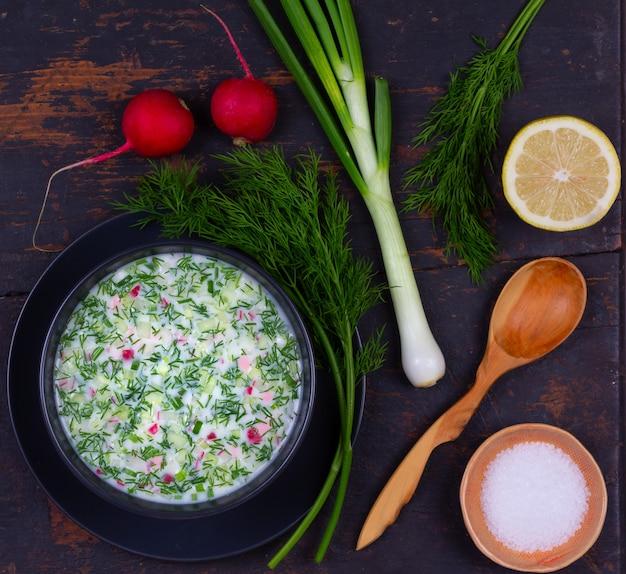 黒いテーブルの上の野菜とkvassとケフィアからロシアの夏冷たいスープオクローシカ Premium写真