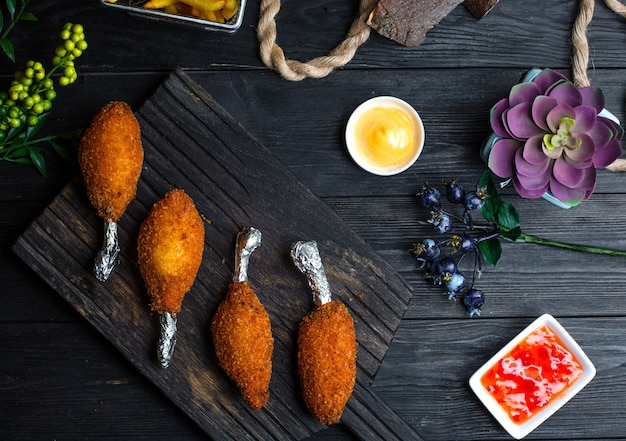 Kyiv cotletes with sauces on wooden board Free Photo