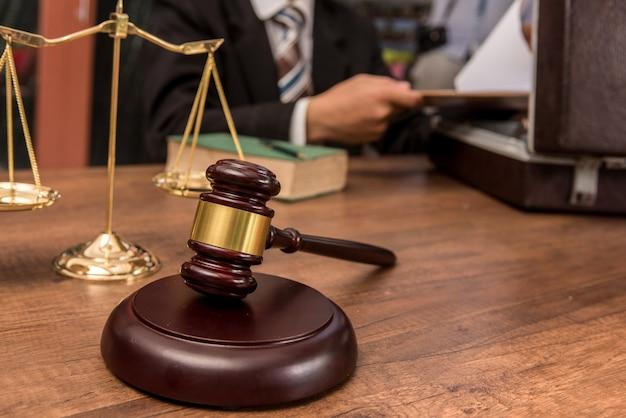 法廷のテーブルにある書類と木製の小lを扱う法廷弁護士。 Premium写真