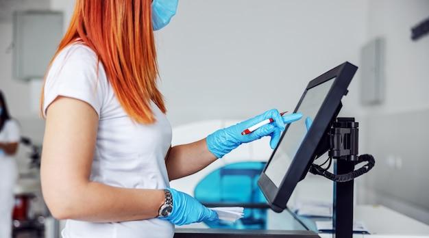 実験室に立ち、コンピュータを使用してcovid-19陽性患者のデータを入力する実験室の助手。 Premium写真