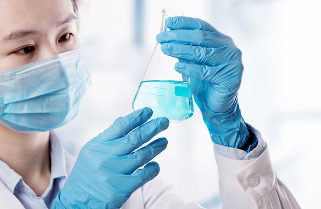 Laboratory beaker in analyst's hand in plastic glove Premium Photo