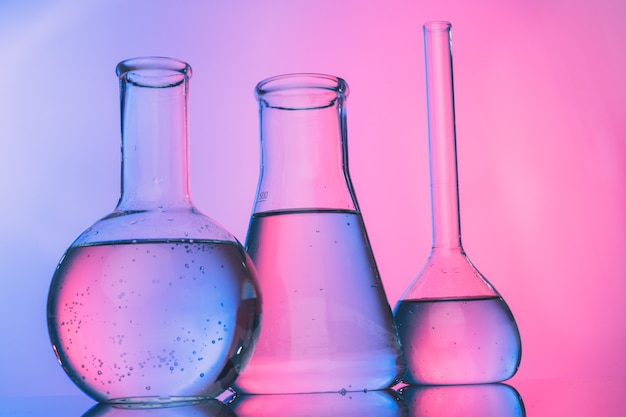 Laboratory glass tubes with chemicals on bright pink Premium Photo