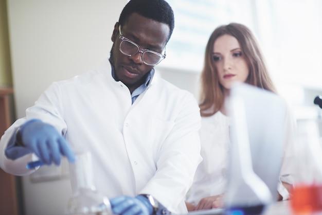 I laboratori di laboratorio conducono esperimenti in un laboratorio chimico in fiasche trasparenti. formule di output. Foto Gratuite