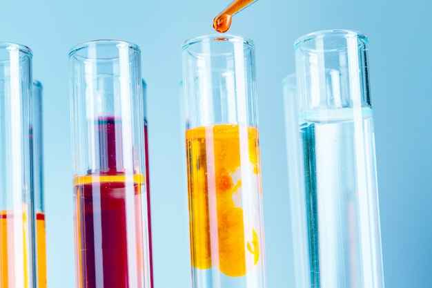 Laboratory test tubes with red and yellow liquids on light blue background Premium Photo