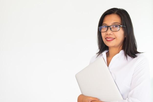 白い背景の上のlabtopのノートを保持している眼鏡をかけている女性実業家 Premium写真