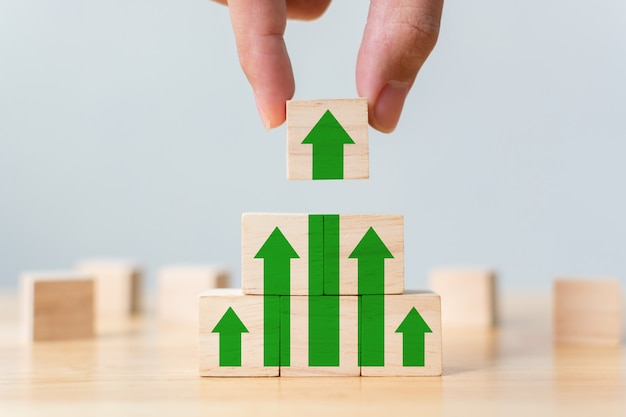 Ladder career path for business growth success process  wood block stacking as step stair with arrow up. hand putting wooden cube block on top pyramid Premium Photo