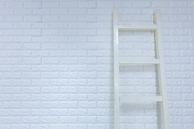 Ladder on white brick wall Premium Photo
