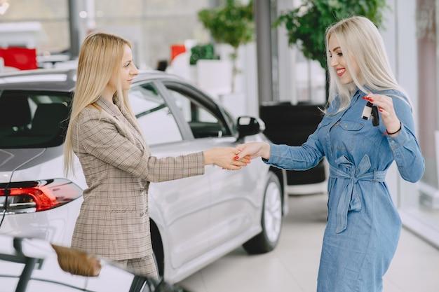 Signore in un salone di automobile. donna che compra l'auto. donna elegante in un vestito blu. il manager dà le chiavi al cliente. Foto Gratuite