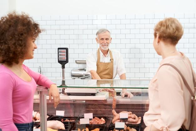Signore che scelgono prodotti a base di carne cruda dietro il bancone. Foto Gratuite