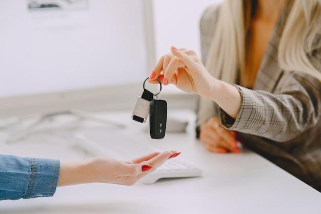 カーサロンの女性。車を買う女性。青いドレスを着たエレガントな女性。マネージャーはクライアントを支援します。 無料写真