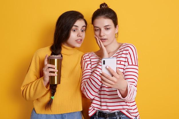 Дамы с умным телефоном в руках и кофе на вынос Бесплатные Фотографии