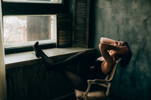 Lady in black lingerie and stockings stretches her legs on windowsill sitting in the chair Free Photo
