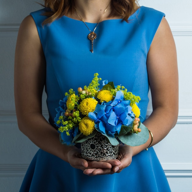 Free Photo Lady In Blue Dress Holding A Bouquet Of Blue And Yellow Flowers