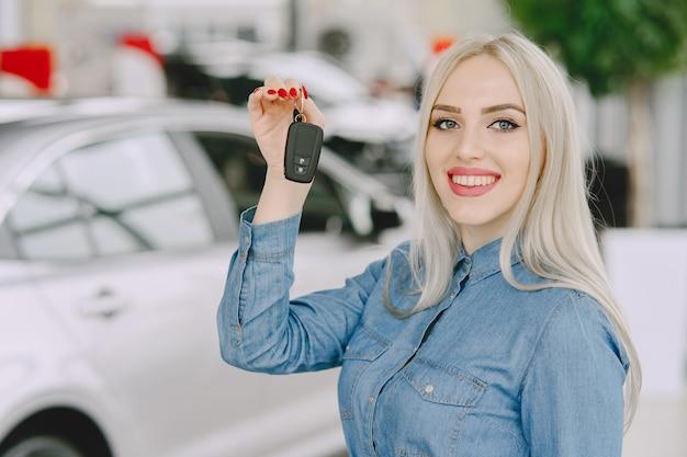 Signora in un salone di automobile. donna che compra l'auto. donna elegante in un vestito blu. Foto Gratuite