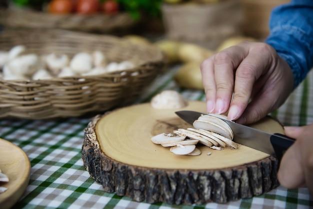 Lady cooks fresh champignon mushroom vegetable in the kitchen Free Photo