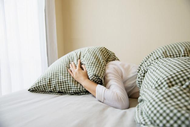 여자는 침대에 베개로 그녀의 머리를 커버 무료 사진