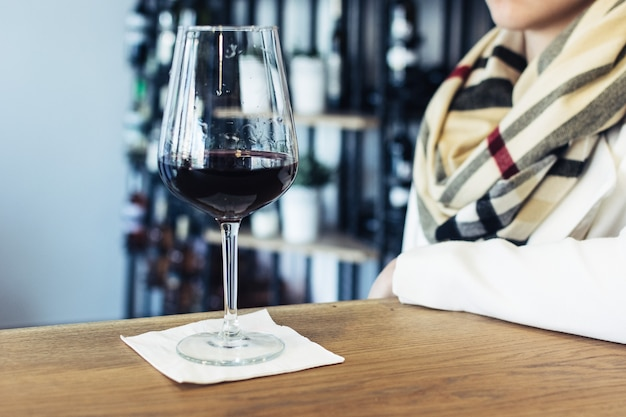 Lady drinking her glass of red wine in a wineshop Free Photo