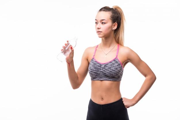 Acqua potabile della signora da una bottiglia trasparente su un bianco Foto Gratuite