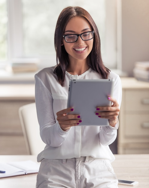Lady in eyeglasses is using a digital tablet. Premium Photo