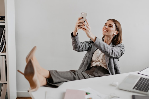 Signora in abito grigio e scarpe décolleté beige prende selfie sul posto di lavoro contro il muro bianco. Foto Gratuite