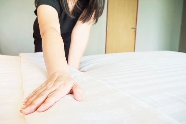 Lady hands set up white bed sheet in hotel room Free Photo