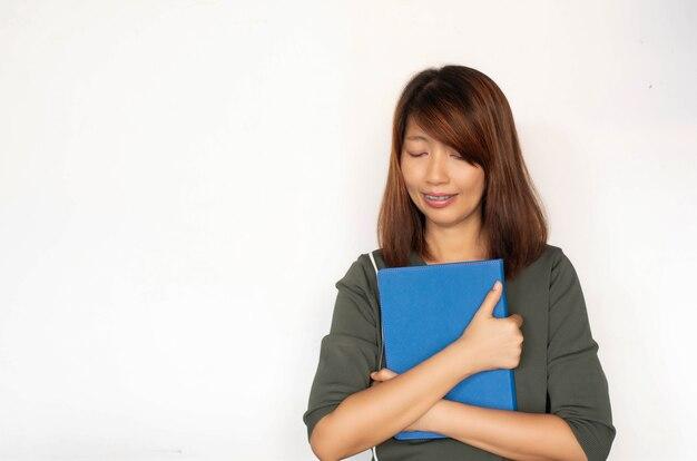 彼女の腕に本を抱き締める女性、下向きにして笑顔、モデルのポーズ Premium写真
