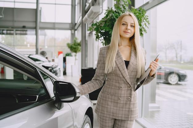 자동차 살롱에서 레이디. 차를 사는 여자. 갈색 정장에 우아한 여자입니다. 무료 사진