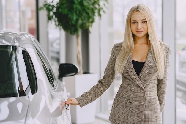 カーサロンの女性。車を買う女性。茶色のスーツを着たエレガントな女性。 無料写真