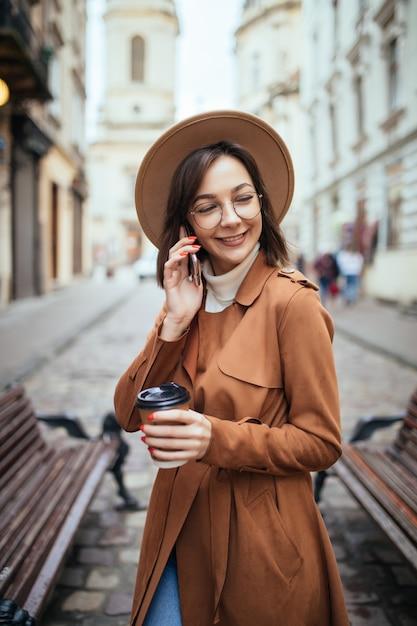 Леди в коричневом пальто разговаривает по мобильному телефону, гуляя на улице в холодный осенний день Бесплатные Фотографии