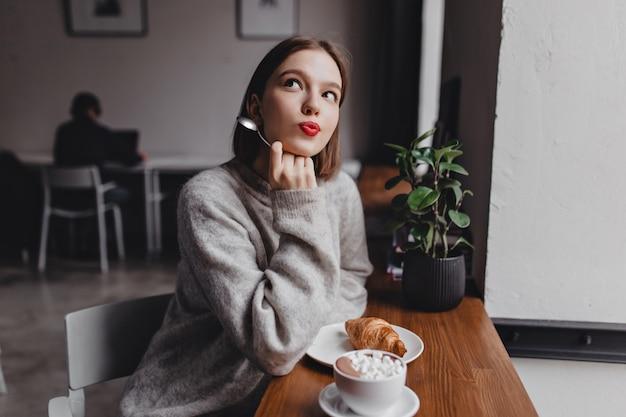 カフェで夢のようにポーズをとる灰色の特大の衣装の女性。クロワッサンとカプチーノとテーブルで若い女の子の肖像画。 無料写真
