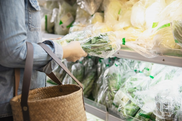 Lady is shopping fresh vegetable in supermarket store Free Photo