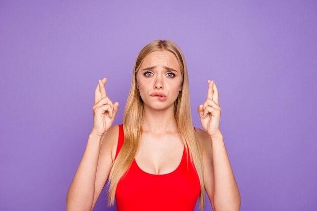 Дама, скрестив указательные пальцы, загадывает желание изолирована на фиолетовом Premium Фотографии