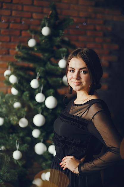 Lady near a christmas tree. Free Photo