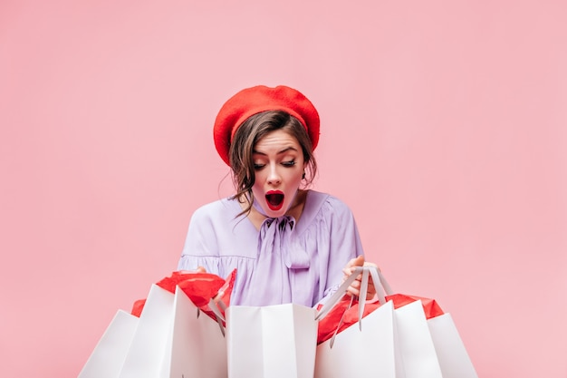 Lady in red beret looks in amazement at white paper bags after shopping. Free Photo