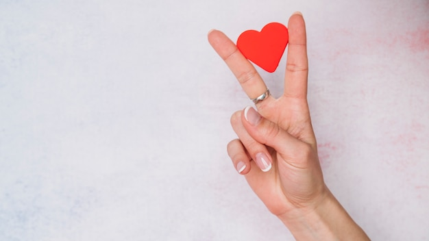 Lady's hand with paper heart between fingers Premium Photo