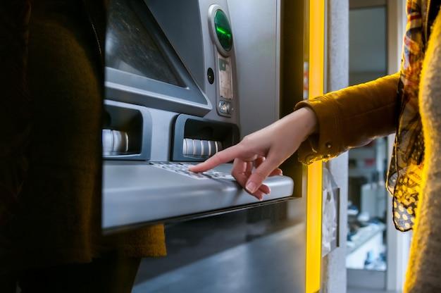 Lady using atm machine to withdraw her money. Premium Photo