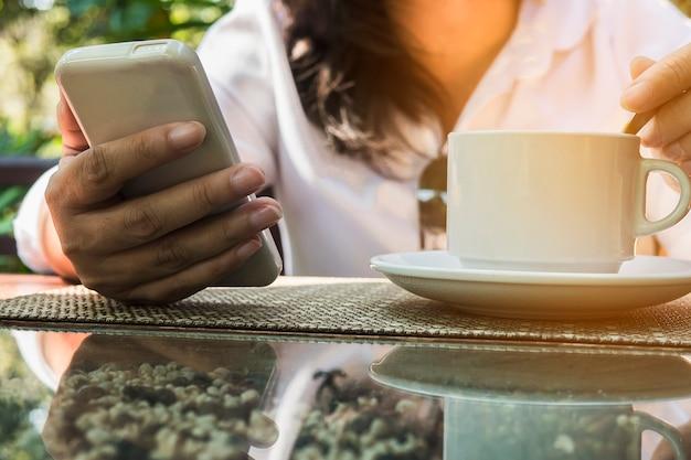 コーヒーを飲みながらモバイルホワイトを使用している女性 無料写真
