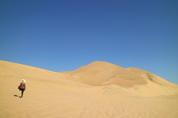 Lady walking on the incredible sand dunes of huacachina desert in ica region of peru, south america Premium Photo