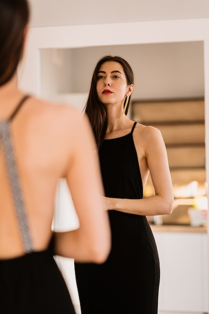Lady wears beautiful black dress looking into the mirror Free Photo