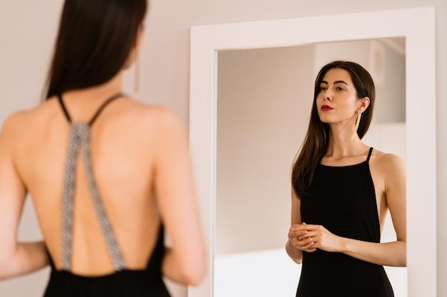 Леди носит красивое черное платье, глядя в зеркало Бесплатные Фотографии