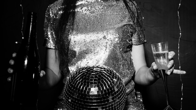 Lady with disco ball, bottle and glass Free Photo